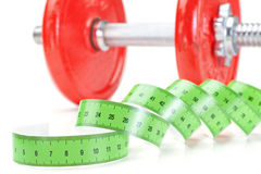 Green measuring meter and dumbbells for fitness. Royalty Free Stock Photo