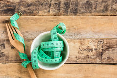 Green measuring tape in ceramic cup on wooden table Stock Photo