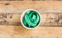 Green measuring tape in ceramic cup on wooden table Stock Photography