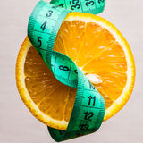 Green measuring tape and orange fruit Stock Image