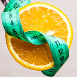 Green measuring tape and orange fruit. Diet healthy eating and slim body concept. Closeup green measuring tape centimeter and orange fruit Royalty Free Stock Photography