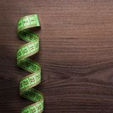 Green measuring tape over wooden background Royalty Free Stock Photo