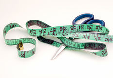 Green measuring tape and scissors Royalty Free Stock Image