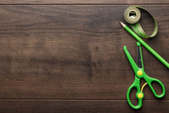 Green measuring tape, scissors and pencil Royalty Free Stock Photos