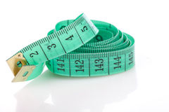 Green measuring tape, symbol of accuracy, on white Royalty Free Stock Photography