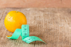 Green measuring tape and tangerine on wooden table Royalty Free Stock Photo