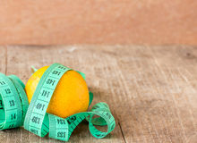 Green measuring tape and tangerine on wooden table Royalty Free Stock Images