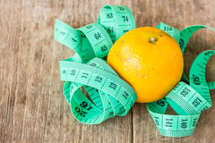 Green measuring tape and tangerine on wooden table Stock Photos