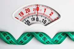 Green measuring tape on weight scale. Dieting Stock Image