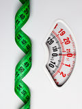 Green measuring tape on weight scale. Dieting Royalty Free Stock Image