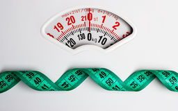 Green measuring tape on weight scale. Dieting Royalty Free Stock Photography