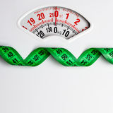Green measuring tape on weight scale. Dieting Stock Photography