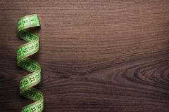 Green measuring tape over wooden background Stock Photo