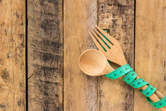 Green measuring tape and wooden spoon and fork Royalty Free Stock Images