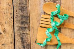 Green measuring tape and wooden spoon and fork Royalty Free Stock Photography
