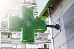 Green, medical cross, Pharmacy, Neon Sign, Green ross, buildin. Green medical cross attached to the pharmacy building. Pharmacy Neon Sign. Green Cross sign on royalty free stock image