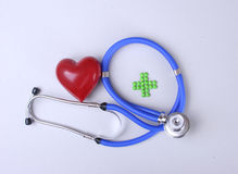Green medical cross sign stethoscope red heart Stock Photo