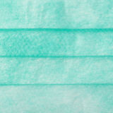 Green medical surgical protective mask texture as abstract background Royalty Free Stock Images