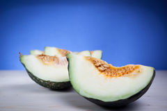 Green melon. Slices on a wooden table over a blue bright background Stock Photography