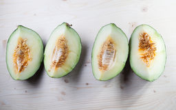 Green melon. On a wooden table Stock Photography