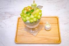 Green melon ball shape are arranged on the top of bingsu (korean ice-cream style) and decorated with green tea ice-cream and mint. Leaf on the wood plate and royalty free stock photo