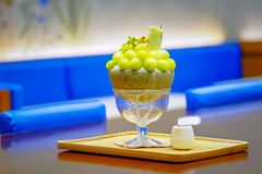 Green melon ball shape are arranged on the top of bingsu (korean ice-cream style) and decorated with green tea ice-cream and mint. Leaf on the wood plate and stock images