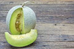 Green melon sliced on wooden table Stock Photography