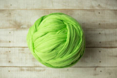 Green merino wool ball. On wooden background Stock Image