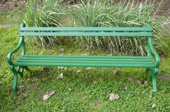 A Green, Metal Bench Amidst Greenery at a Park Stock Images