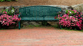 Green metal bench on gorgeous brick patio Royalty Free Stock Image