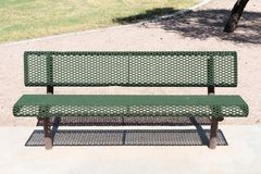 Green metal bench in park on the concrete royalty free stock photos