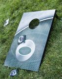 Metal corn hole game on grass. A green metal corn hole game is laying on tall green grass with bean bags around it royalty free stock photo