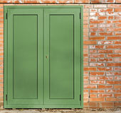 Green Metal Door on a Brick Wall Stock Images