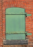 Green metal door in a brick wall. Royalty Free Stock Photos