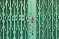 Green metal door with look and bullet holes around it stock photos