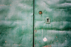 Green metal door. An old, rusty and grungy metal door with a keyhole Stock Photo