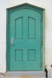 Green metal door in a white plaster wall Stock Image