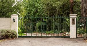 Green metal driveway entrance gates set in brick fence. Green wrought iron driveway entrance gates set in brick fence with garden trees in background Stock Photography
