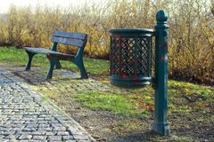 Green metal dustbin trash can stands on the grass nearby a metal bench with wood planks in the city park. Sidewalk with cobblestones is in front of litter bin Stock Image