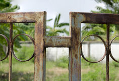 Green Metal fence become rusted through years of disregard. Green Metal fence become rusted through years of disregard beside building Stock Images