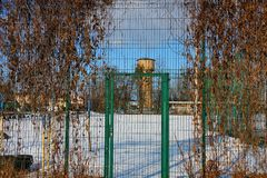 Green metal fence of the grid and a closed door overgrown with dry vegetation on the street in white snow. Green metal fence of the grid and a closed door royalty free stock photography