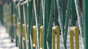 Green metal fence in the winter on a Sunny day. The shadow on the fence from a walking person stock footage