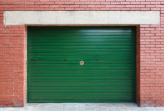 Green metal garage gate in red brick wall Stock Images
