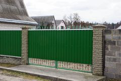 Green metal gate and part of a long fence in the street royalty free stock images