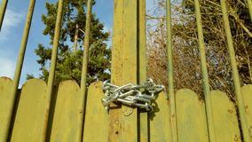 Green metal gates. Lightly rusted green metal gates fastened with new silver metal chain under bright blue and white sky Royalty Free Stock Photo