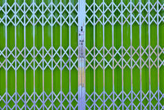 Green metal grille sliding door with pad lock Stock Images