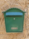 Green metal mail box hanging on yellow concrete house wall. Home mailbox Royalty Free Stock Photos
