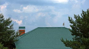Green metal roof with chimney and  weathervane Stock Photography