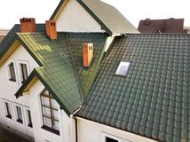 Green metal shingled house roof with attic plastic window and brick chimney.  stock photos