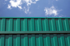 Green metal vertical fence against blue sky with clouds Royalty Free Stock Photography